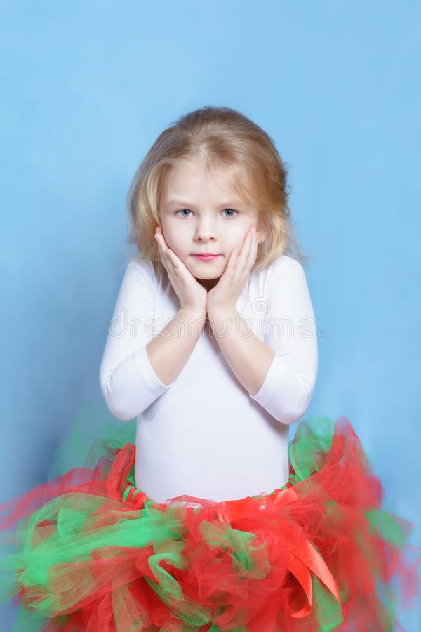 Little Girl Ballerina in Colorful Tutu Portrait. Blond Child in Pretty Ballet Skirt on Neutral Studio Background. Cute Shy Model Posing with Hands on Face royalty free stock photo