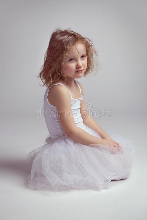 Little girl - ballerina tired and sitting on the floor stock photo