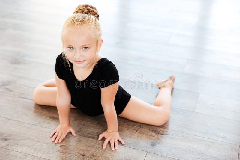 Little girl ballerina stretching in dance studio stock photography
