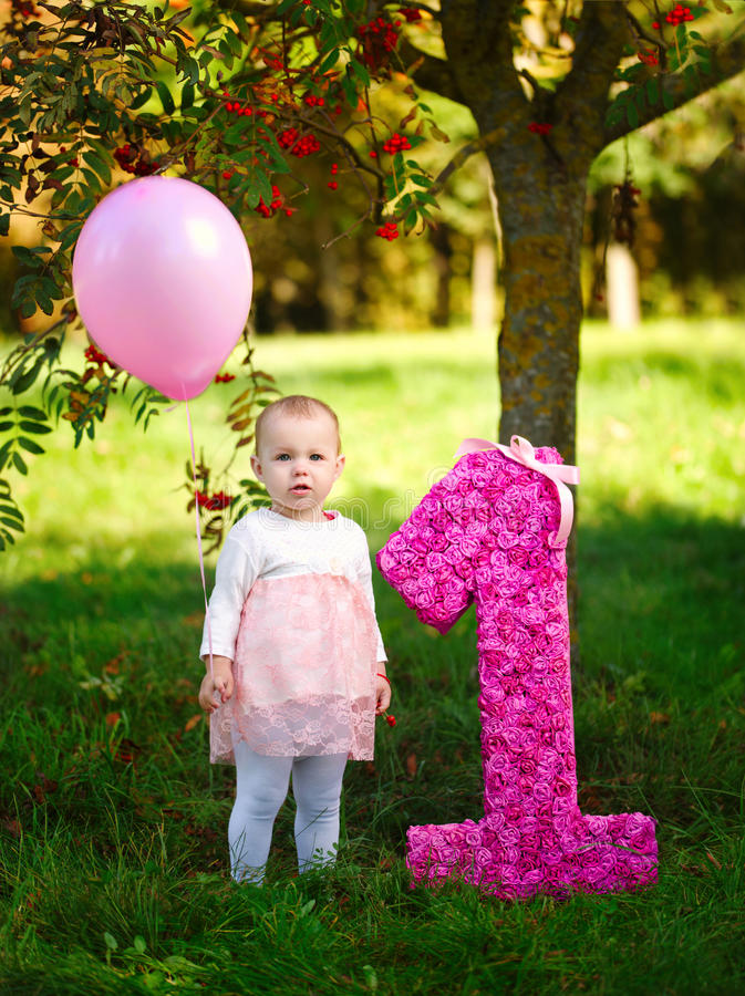 Little girl with balloon and big one. Photo of cute little girl with balloon and big one royalty free stock image