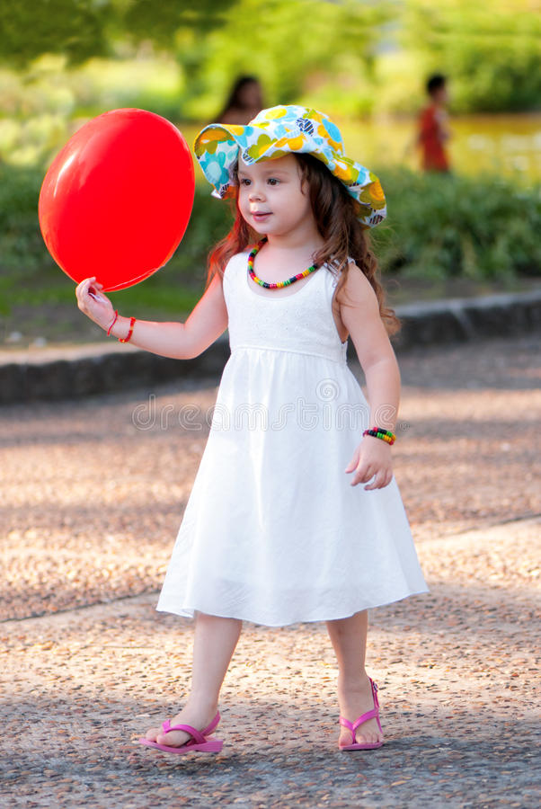 The little girl with balloon in park stock photos