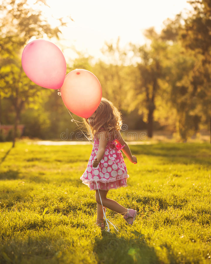 Little girl with balloons. Walks in the park outdoors. Man is unrecognizable stock images