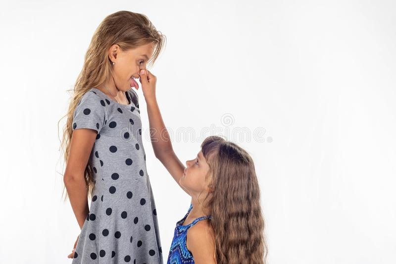 Little girl barely reached for the nose of a tall girl. Little girl barely reached for the nose of a tall  girl stock photo