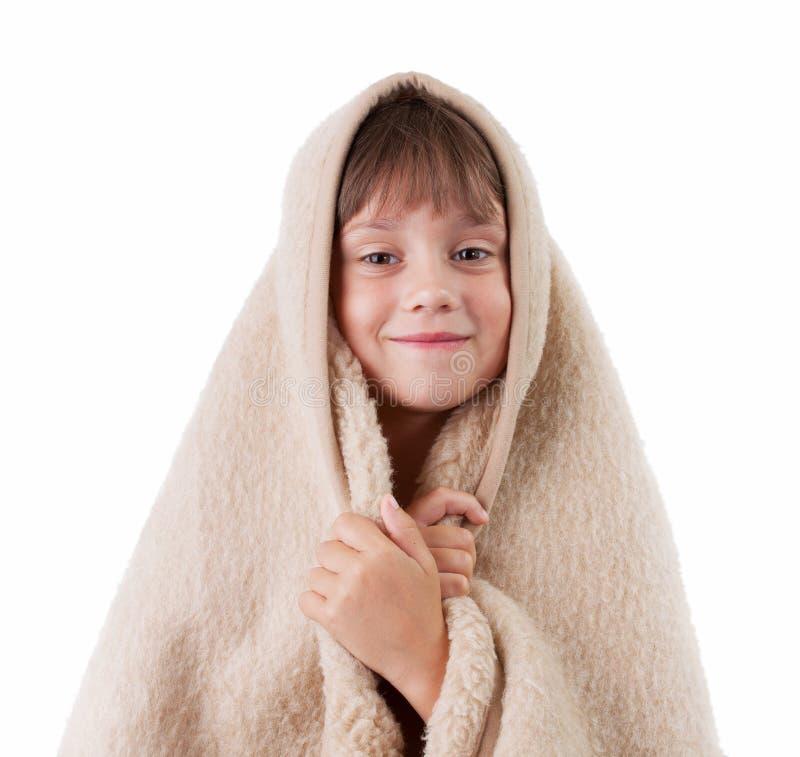 Little girl is basking under a blanket
