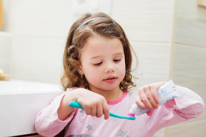 Little girl in bathroom putting a toothpaste on toothbrush stock photos