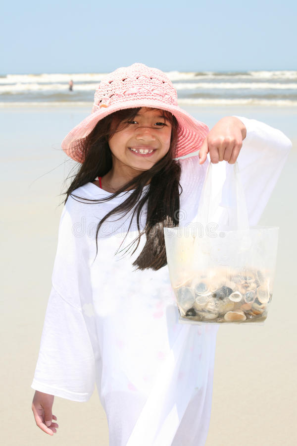 Little girl at beach with bag of shells royalty free stock photography