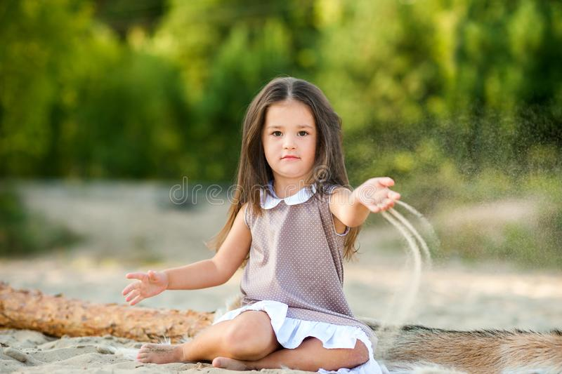 Little girl on the beach playing with sand and having fun stock images