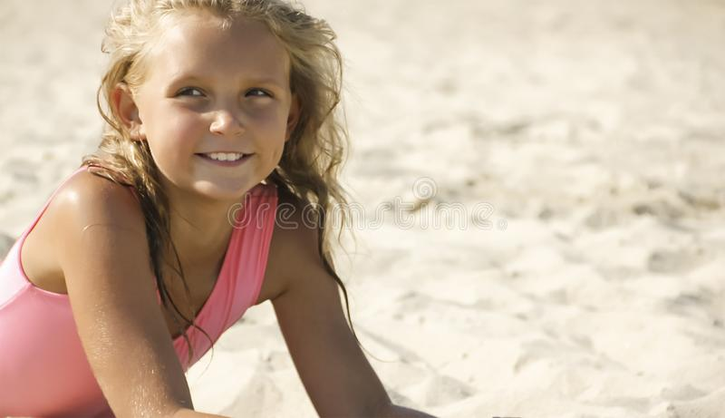 Little girl on the beach in the sand royalty free stock image