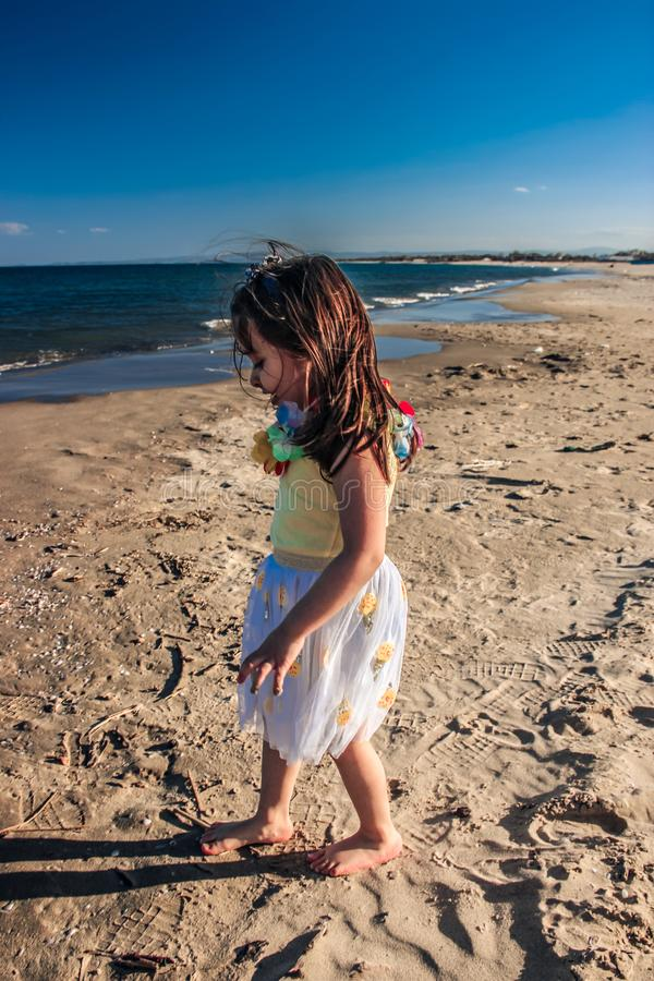 Little girl at beach, summer dressed child girl walks seaside on the sand stock photography