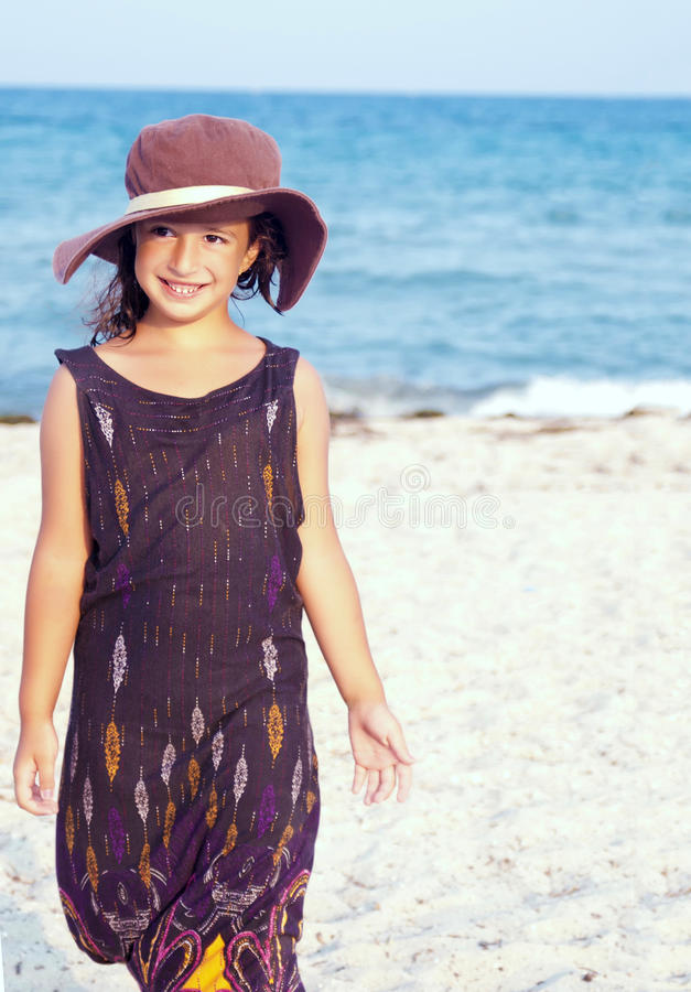 Little girl on the beach wearing funny hat. stock photography