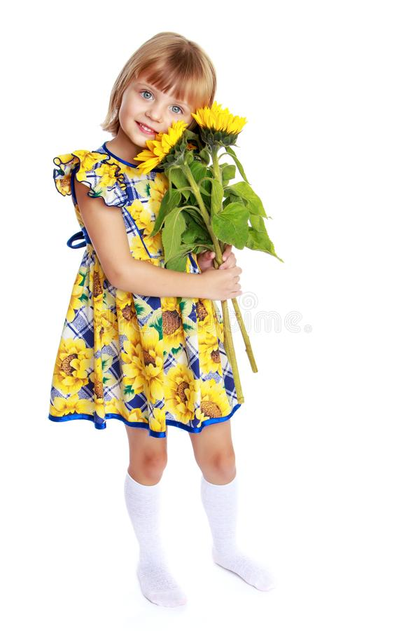 Little girl with flowers of sunflower. stock image