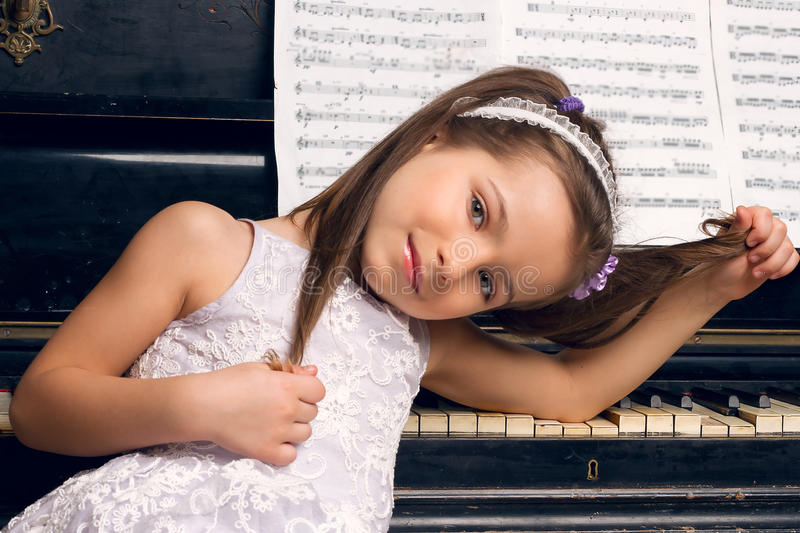 Girl in a beautiful dress sits at the piano