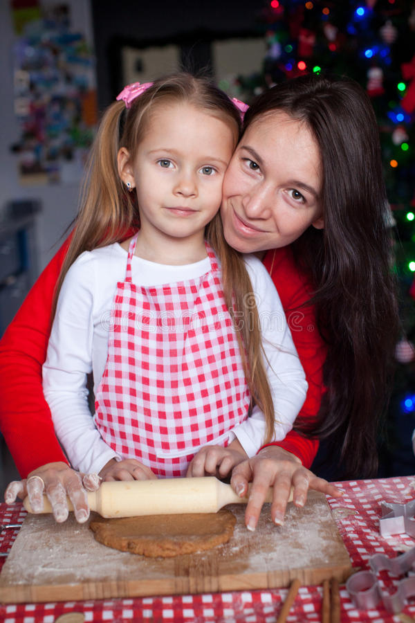 Little girl with beautiful mother baking Christmas. Gingerbread cookies together. This image has attached release royalty free stock images