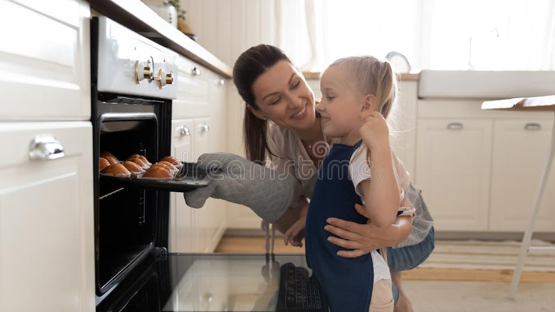 Little girl and beautiful mother taking muffins out the oven royalty free stock image