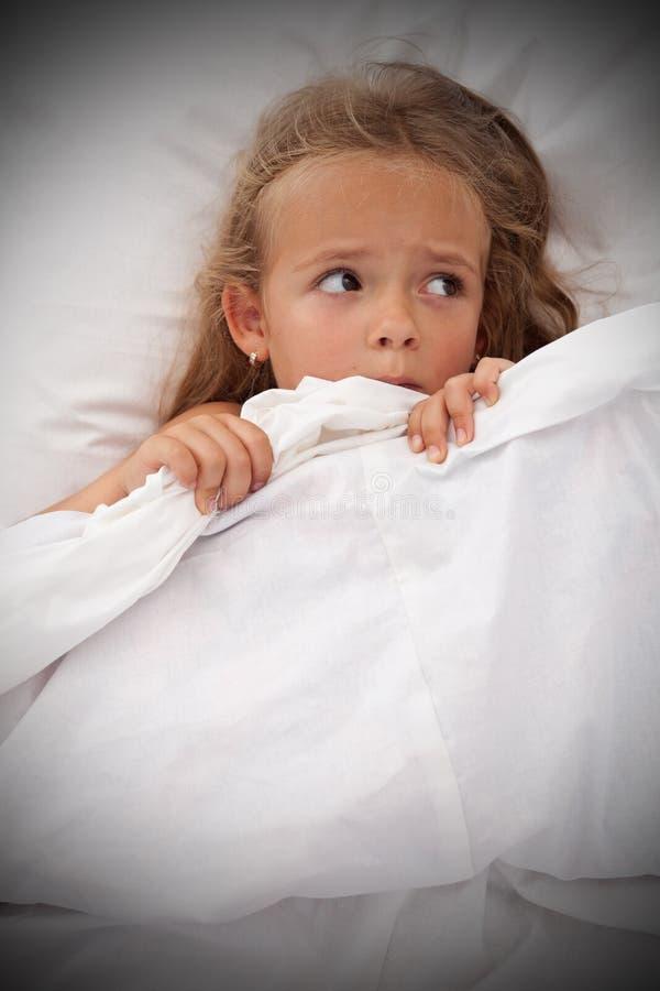 Little girl in bed awaken by nightmares