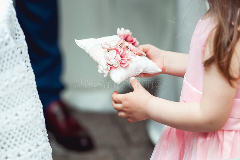 Little girl in a beige dress holding ring for the bride for the wedding ceremony in church. Little girl in a beige dress holding in hands ring for the bride for royalty free stock photos