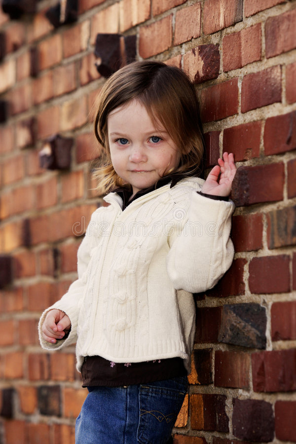 Little girl being a mini-model. Little girl posing in front of brick wall stock images