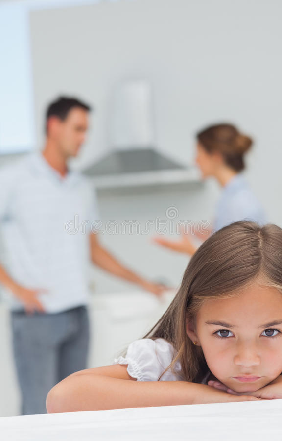 Little girl being sad while parents are quarreling royalty free stock images