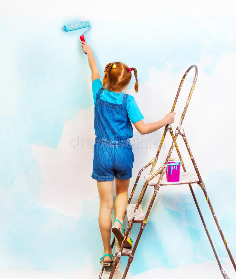 Little Girl In Bib And Brace Stands On A Ladder Stock