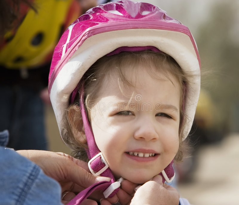 Little girl in a bicycle helmet. Young girl having a bicycle helmet snapped on her head smiles at the camera royalty free stock photos