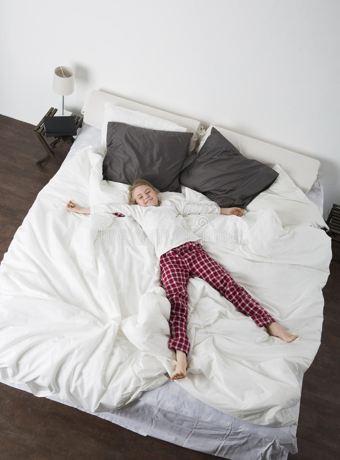 Little Girl in a big bed stock image