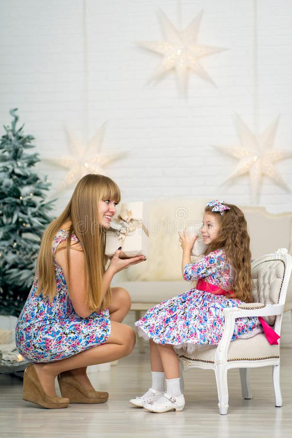 Little girl with a big Christmas present together with mom poses near the Christmas tree stock photography