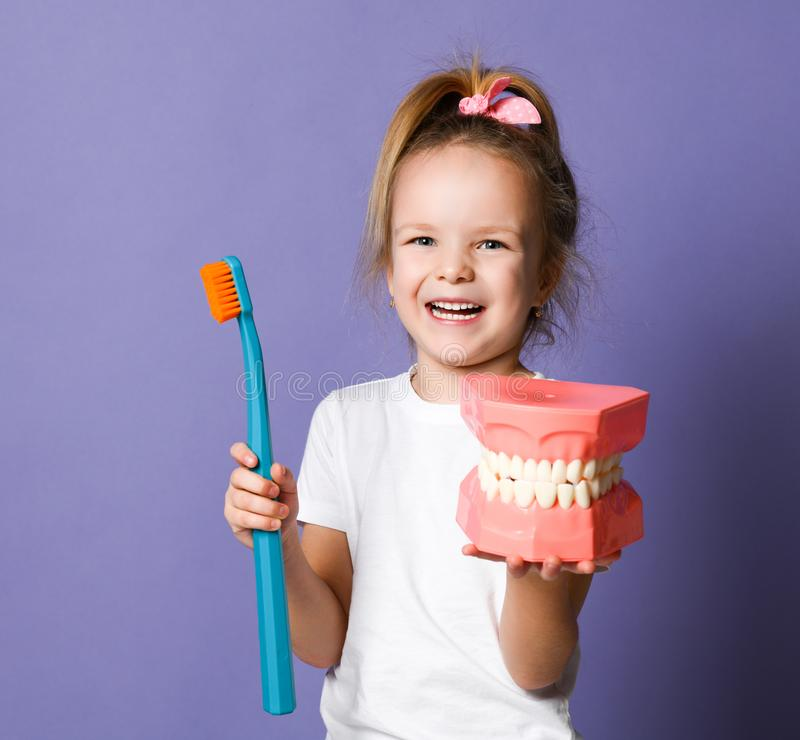 Little girl with big dental implant model and toothbrush studies how to clean teeth properly on purple. Little blonde girl in white t-shirt with big dental royalty free stock photos
