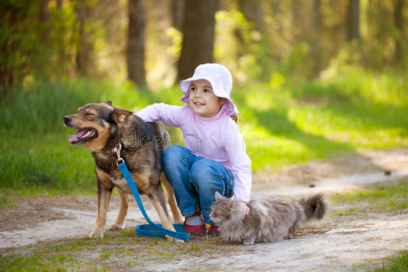 Little girl with big dog and cat. In the forest stock image