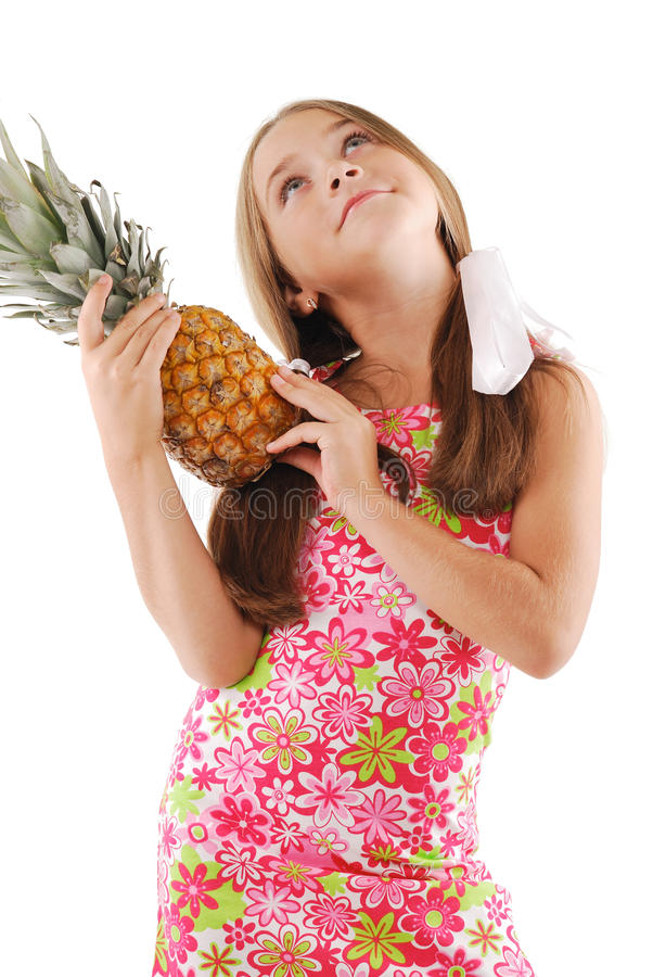 Little girl with big pineapple. Little girl posing with big pineapple royalty free stock photography