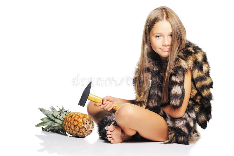 Little girl with big pineapple and hammer. Little girl posing with pineapple dressed as prehistoric stock photo