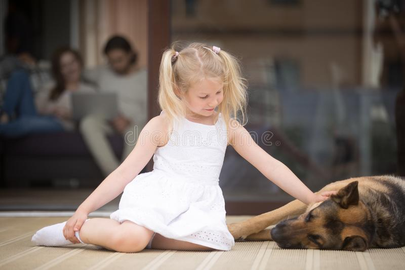 Little girl with big shepherd dog on terrace at home stock photography