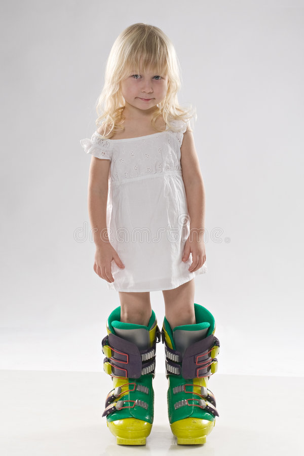 Little girl in in big ski boots stock images