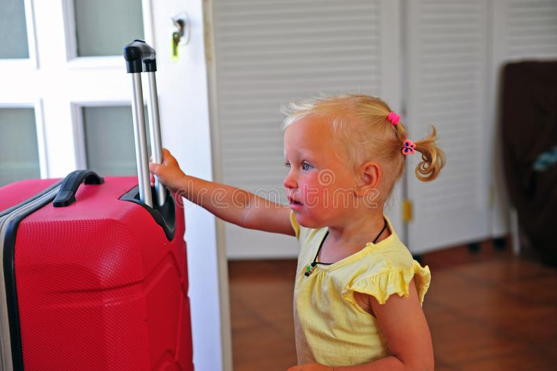 Little girl with big travel suitcase stock photography