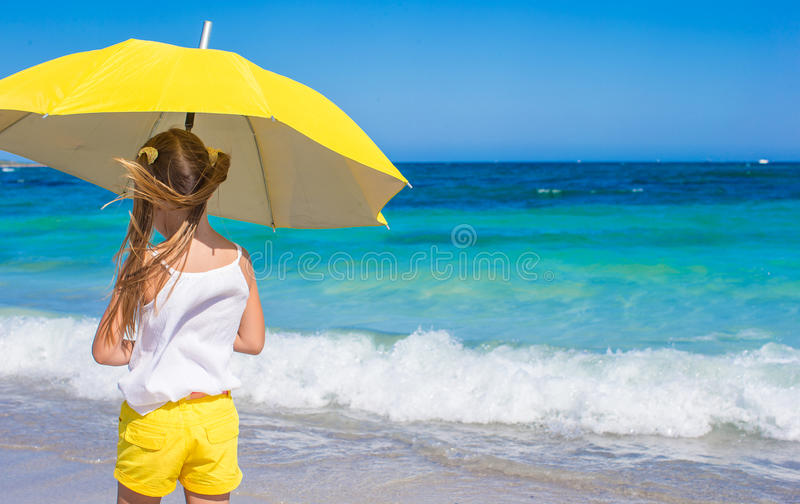 312c0f25a4e62 Little girl with big yellow umbrella walking on. Little cute girl with big  blue umbrella