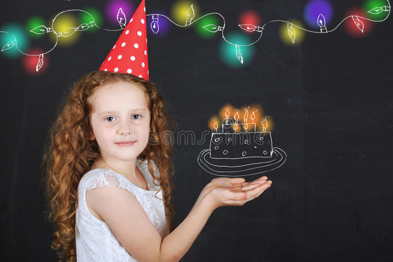 Little girl in birthday hat hold a birthday cake drawing on blackboard. stock image