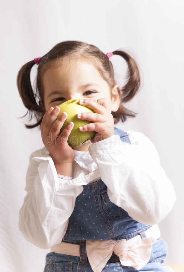 Little girl biting a green apple stock photography