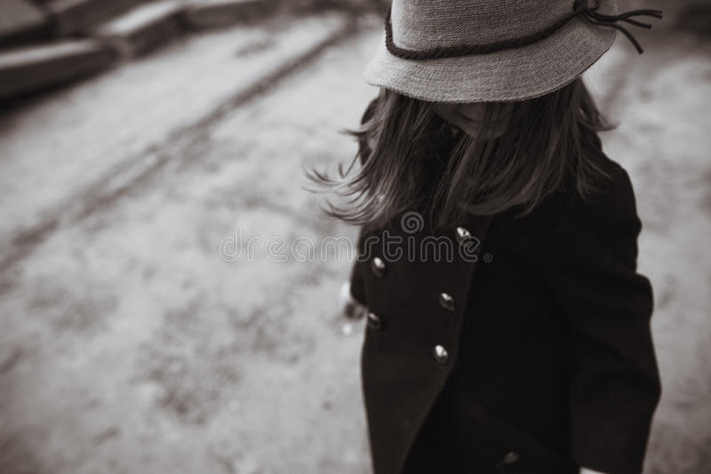 Little girl in a black coat and hat royalty free stock photo