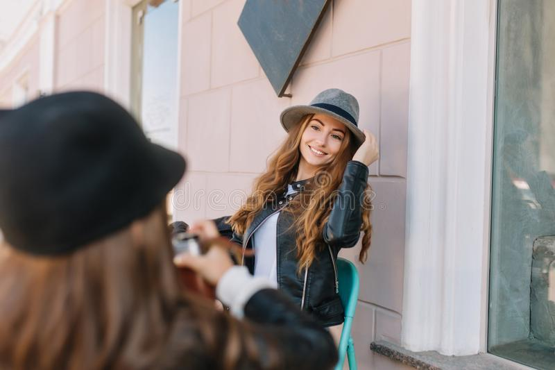 Little girl in black hat holding camera going to make picture of smiling mother sitting in front of building. Portrait stock photo