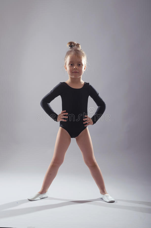 Little girl in black tights dancing on a gray background. stock photo