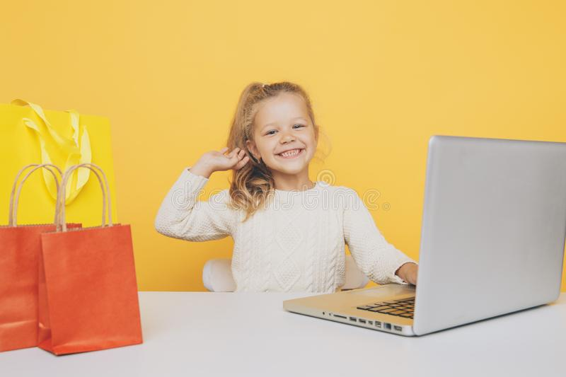 Little girl blogger using laptop and making shopping online. Little girl blogger using laptop and making shopping online stock image