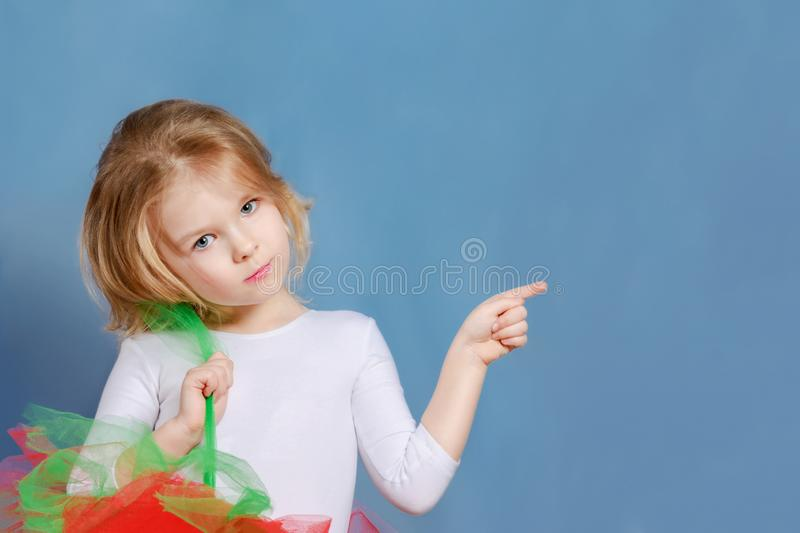 Little girl with blond hair on a blue background. A beautiful child points to a blank space for an inscription or text. royalty free stock photo
