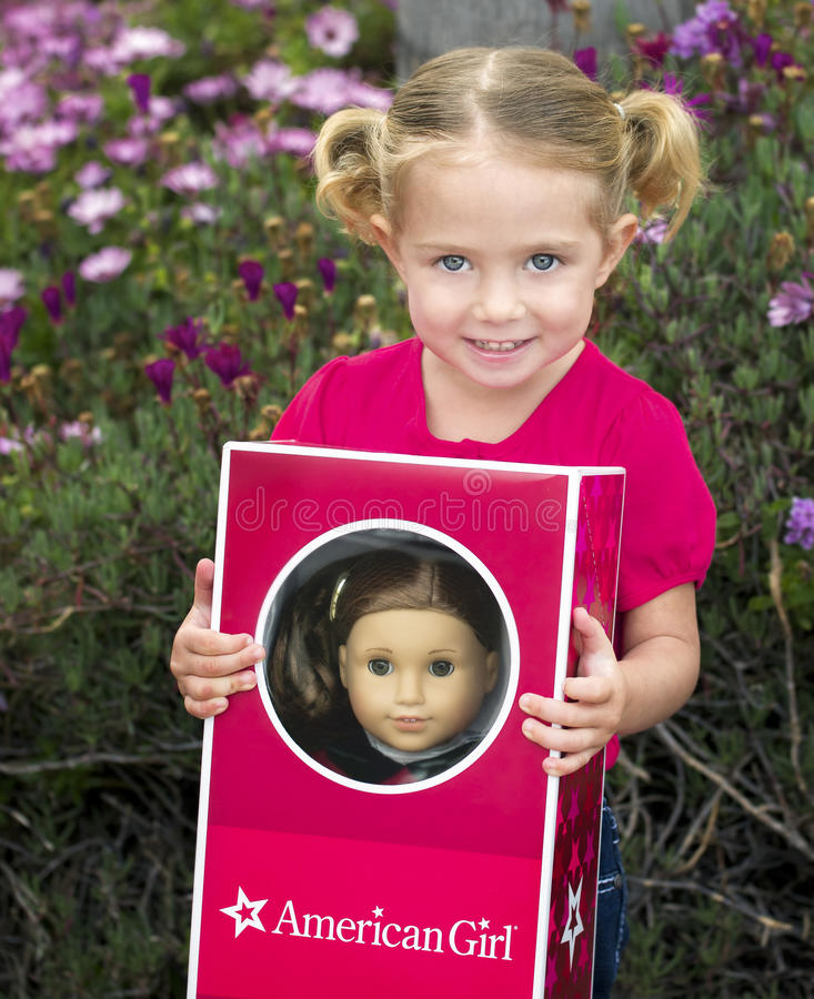Toddler with her American Girl Doll stock photography