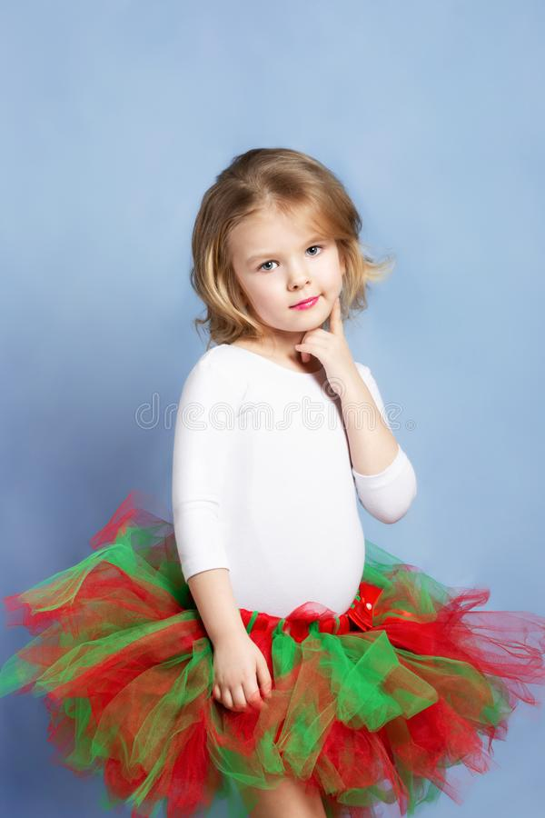 Little girl with blond hair poses on blue background. Beautiful cute baby in a full skirt. royalty free stock photos