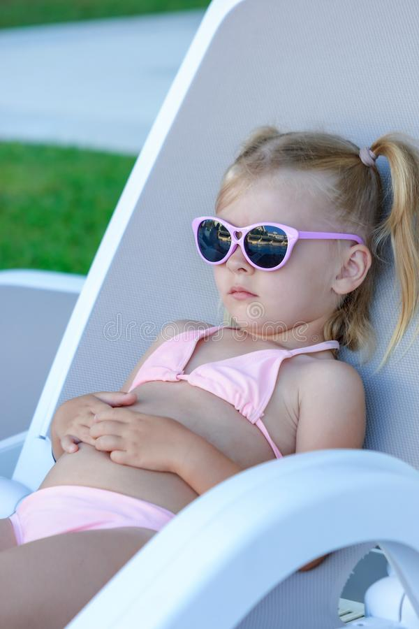 A little girl with blond hair is resting on a lounger. The child put on his sunglasses. Summer photography. stock photo