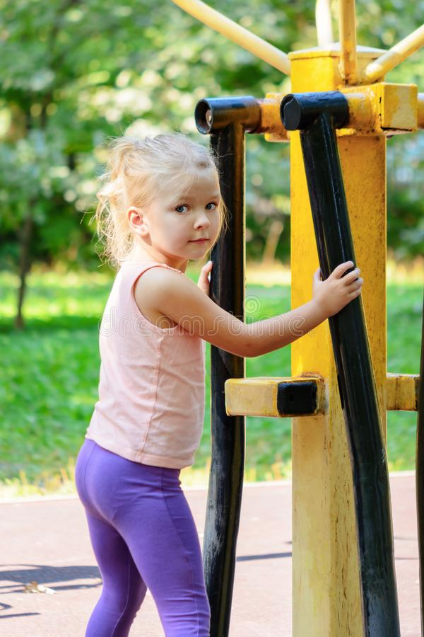 Little girl with blond hair on the sports field. The child is engaged on the street training apparatus. royalty free stock photography
