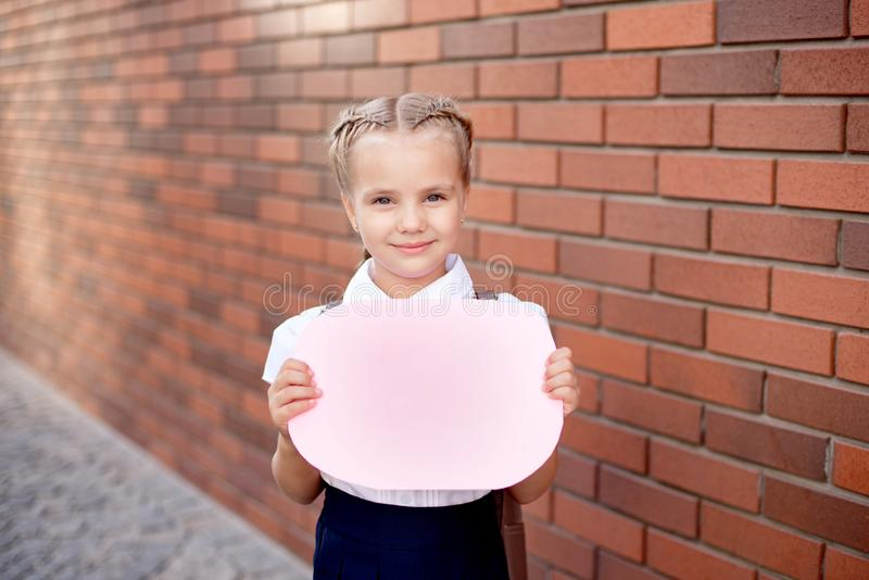Little girl with blond hair in a white shirt and blue skirt holds an empty board near the upper wall.  royalty free stock image