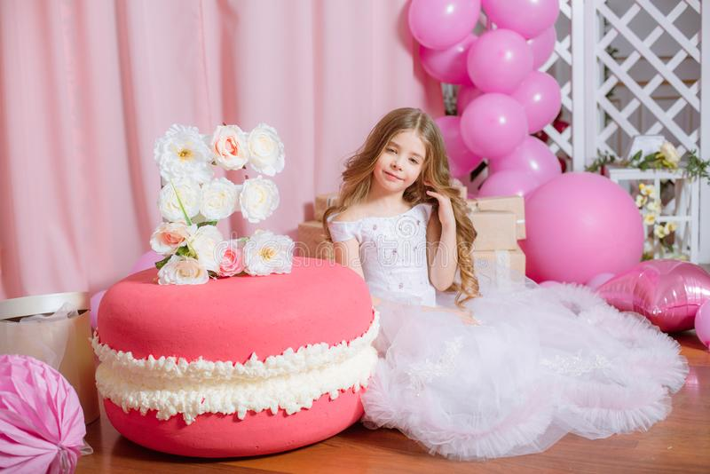 Little girl with blond long hair celebrate Happy Birthday Party with rose decor stock photos