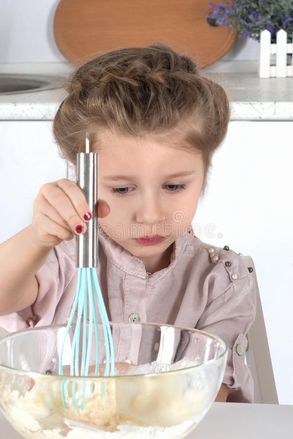 The little girl the blonde does dough in kitchen of the house. It stirs slowly with a nimbus dough in a glass bowl stock photo
