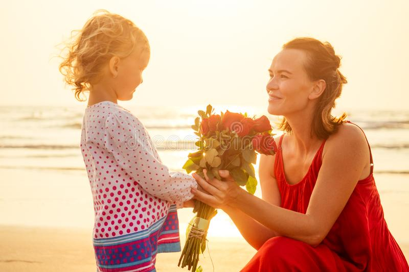 Little girl blonde gives a bouquet of roses to mother on the beach.beautiful mother and daughter with flowers by the sea royalty free stock images
