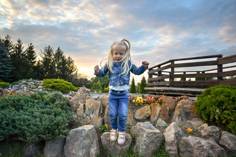 A little girl with blonde hair in jeans stock photo